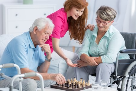 Caregiver helping an elderly couple enjoy a game of chess at home