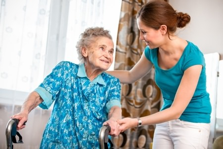 Caregiver Helping Elderly Woman At Home