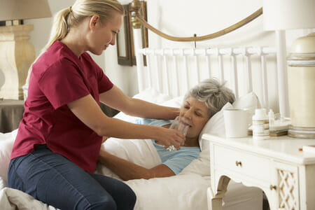 Nurse Helping Senior Patient with Water in Bed