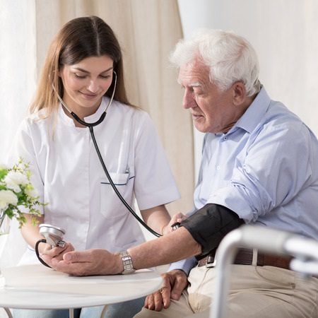 Young Nurse Taking Elderly Man's Vital Signs