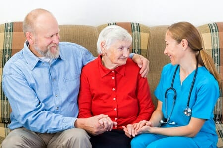 elderly woman and her son with caregiver
