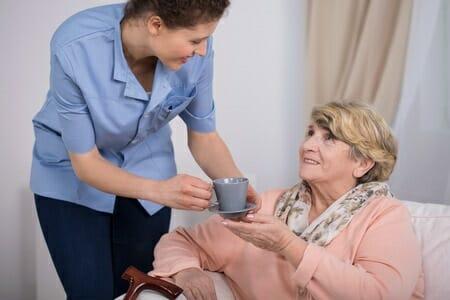Caregiver Serving Tea to Elderly Woman
